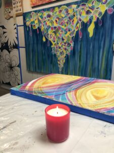 A candle and paintings from the studio of Melynda Van Zee