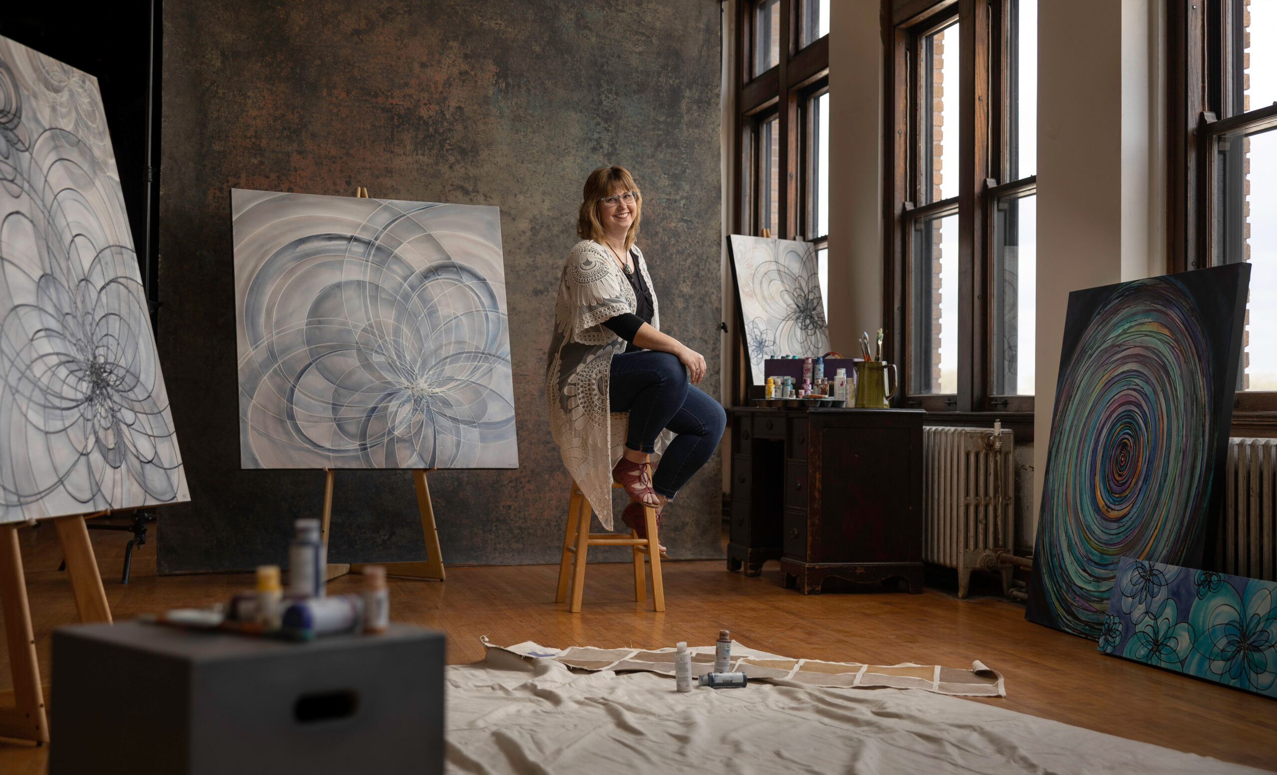 Artist Melynda Van Zee in studio surrounded by large paintings.